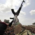 Un soldat ivoirien brandit son arme devant une foule de supporters de Laurent Gbagbo, en mars 2011. AFP PHOTO/ SIA KAMBOU