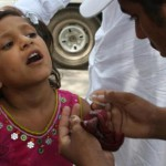 Peshawar, Pakistan, le 18 juillet 2011. Une petite fille reçoit quelques gouttes d'un vaccin contre la polio, dans une gare routière.Karin Brulliard/The Washingt