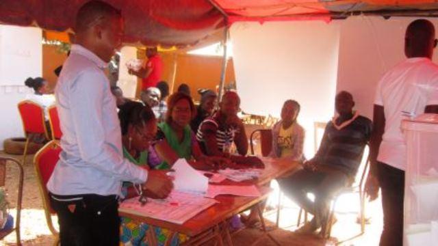 Une ambiance enthousiasmante d'explication du processus de vote entre agents de bureau de vote et électeurs.